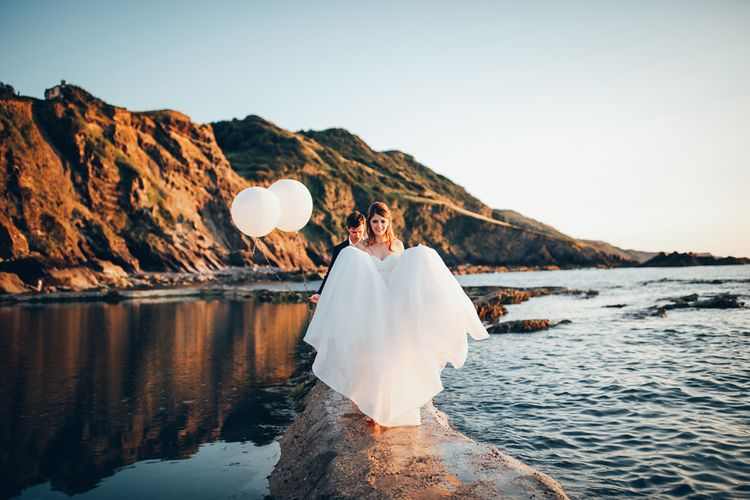 Bride in Strapless Ballgown Dress by Pronovias with Crystal Belt | Groom in Navy Suit with Gypsophila Buttonhole |  Oversized White Balloons | Gypsophila Arch and Giant Balloons for an Outdoor Coastal Wedding | Toby Lowe Photography