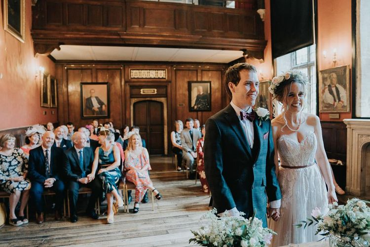Intimate Oxford wedding ceremony with white flower decor and lace detailed dress
