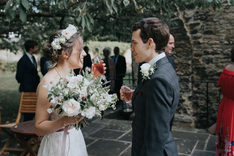 Bride and groom tie the knot at intimate celebration with a white floral bouquet and a flower head crown