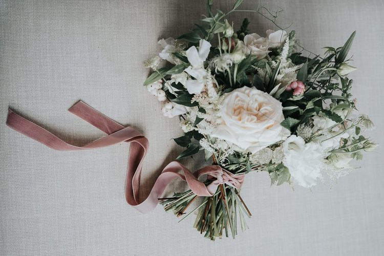 Beautiful white floral bouquet with ribbon detailing at relaxed celebration filled with personal touches