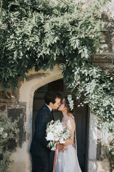 PopBride and groom tie the knot at intimate celebration with a white floral bouquet and a flower head crown