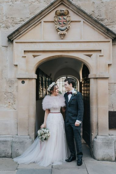 Bride and groom tie the knot at intimate celebration with a bridal shrug and a flower head crown
