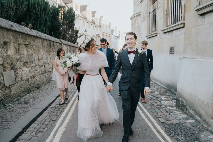 Bride and groom take a walk with their guests at an intimate Oxford wedding with a bridal shrug and a flower head crown