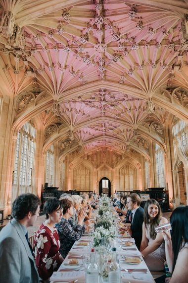 Guests enjoying an intimate and relaxed reception at Bodleian library with white floral centrepieces