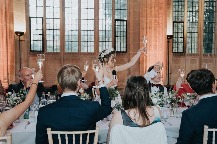 Bride raises her hand for a toast at intimate Oxford wedding reception wearing a floral head crown