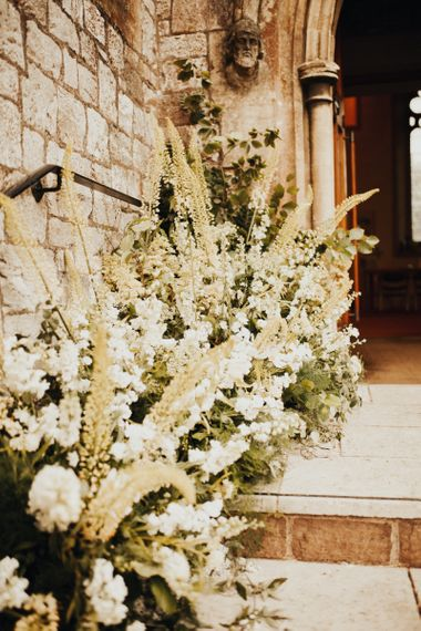 Wedding flowers decorate the church for ceremony
