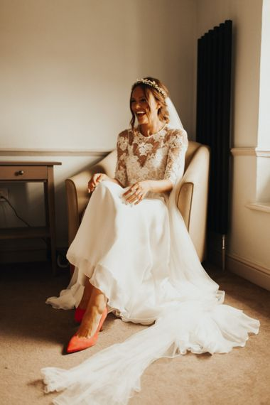Bride in lace sleeved wedding dress with flower crown and pink shoes