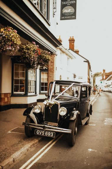 Vintage wedding car for Devonshire wedding  with floral chandelier and foliage table runner