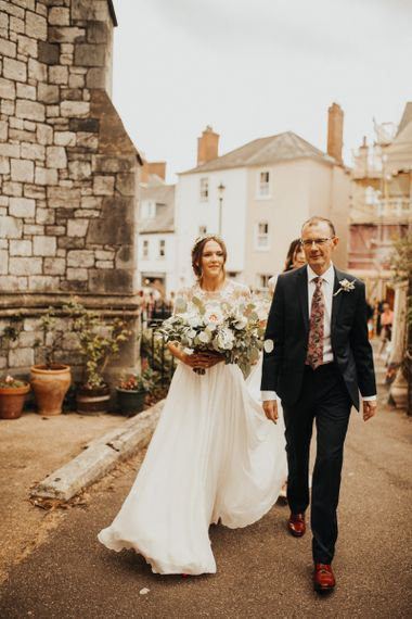 Bride arrives at church with father carrying large bouquet
