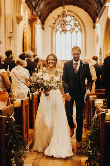 Bride and groom walk back up aisle after church ceremony