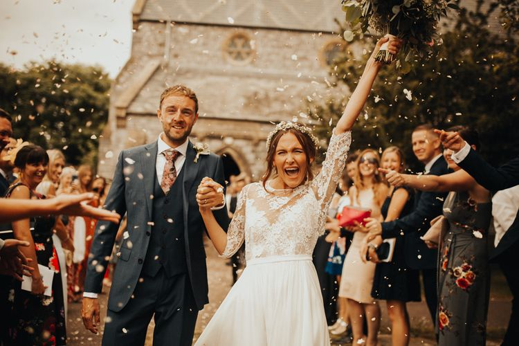 Confetti exit for bride and groom at wedding with floral chandelier and foliage table runner