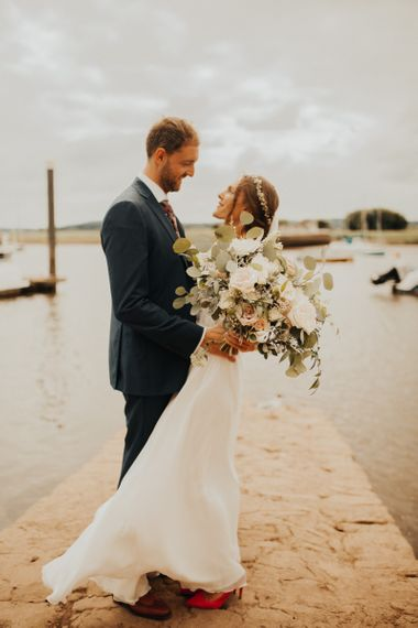 Large bridal bouquet at wedding with foliage table runner