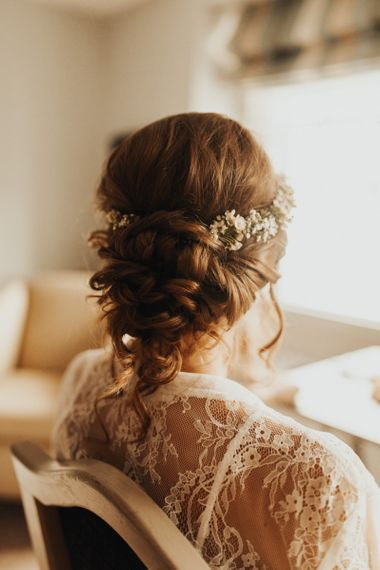 Bridal up do with flower crown at wedding with flower chandelier and foliage table runner