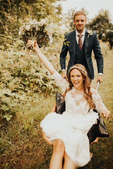 Groom pushes bride in wheelbarrow at Devonshire wedding