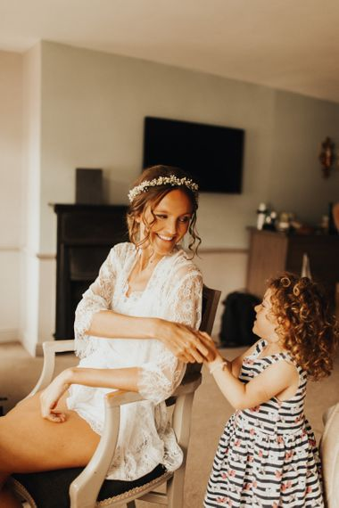 Bridal preparation with bride in lace getting ready robe  and flower crown
