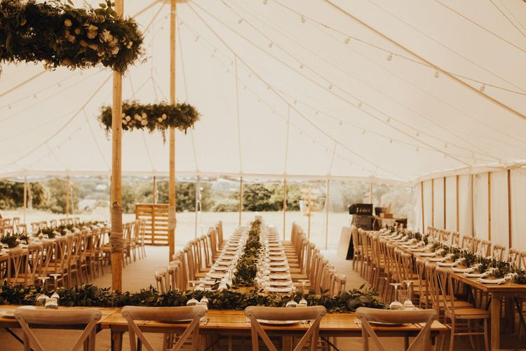 Marquee wedding decor with foliage table runner and floral chandelier