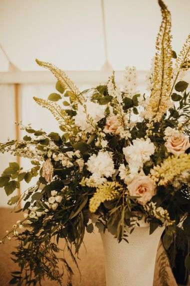 Beautiful floral displays at marquee wedding with foliage table runner