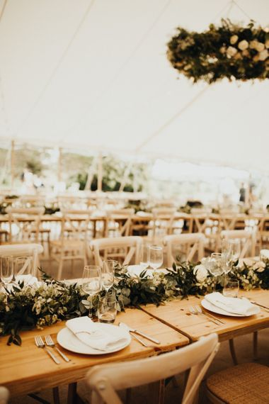 Beautiful marquee wedding decor with foliage table runners