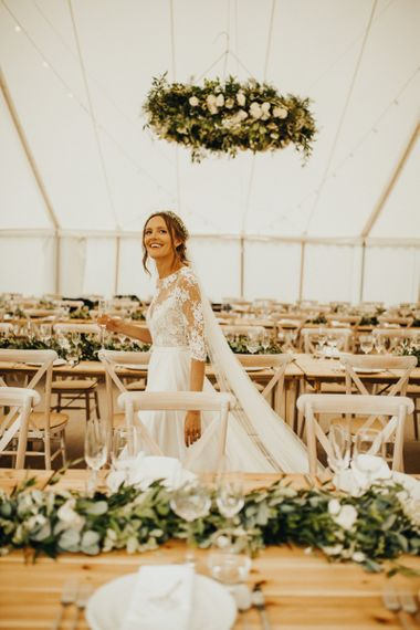 Bride sees marquee wedding decor and foliage table runners