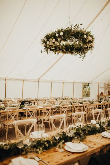 Marquee wedding decor with floral chandelier and foliage table plan