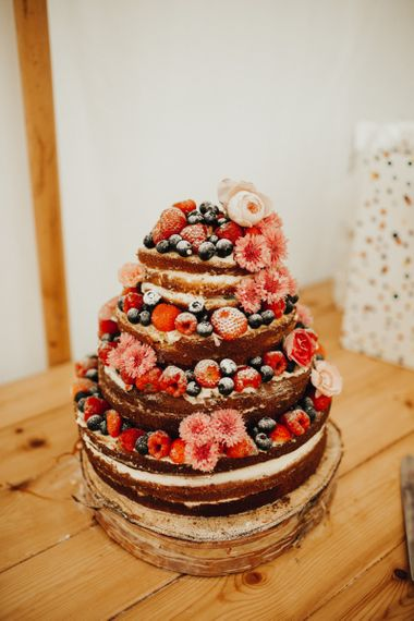 Naked wedding cake adorned in berries with foliage table runner decor