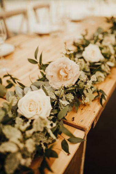 Wedding flowers amongst foliage table runner