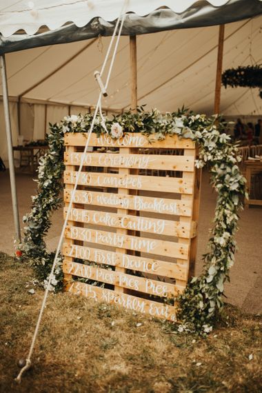 Wooden pallet sign with foliage and flower garland decor