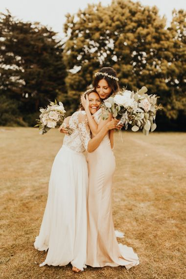 Bride with bridesmaid in pink dress and flower crown