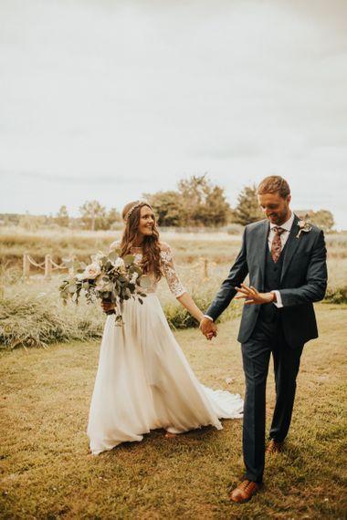 Bride and groom stroll through family garden