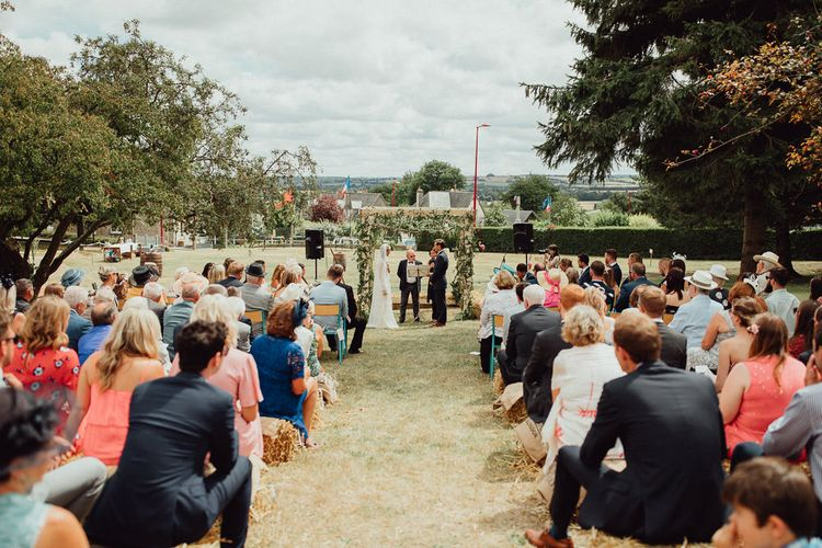 Wedding Ceremony | Bride in Laced Catherine Deane Wedding Dress with Long Sleeves | Groom in Blue Thomas Farthing Suit with Ochre Tie | Guests on Hay Bales | Rustic French Destination Wedding with Homegrown Flowers  | Emily & Steve Photography