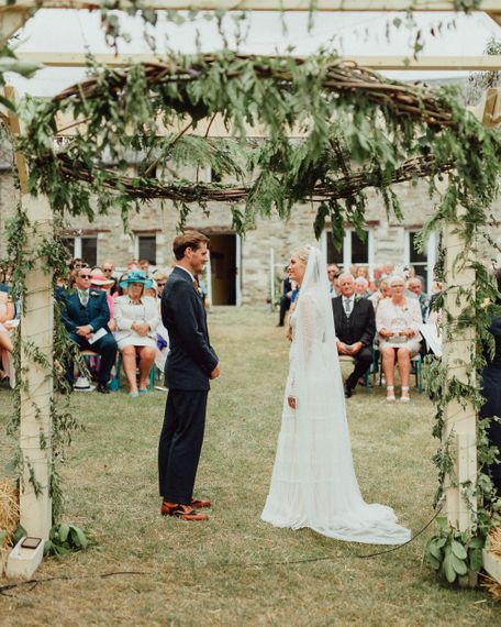 Wedding Ceremony | Foliage Arch | Bride in Laced Catherine Deane Wedding Dress with Long Sleeves | Groom in Blue Thomas Farthing Suit with Ochre Tie | Rustic French Destination Wedding with Homegrown Flowers  | Emily & Steve Photography