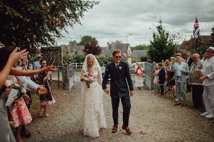 Confetti Moment | Bride in Laced Catherine Deane Wedding Dress with Long Sleeves | Groom in Blue Thomas Farthing Suit with Ochre Tie | Rustic French Destination Wedding with Homegrown Flowers  | Emily & Steve Photography