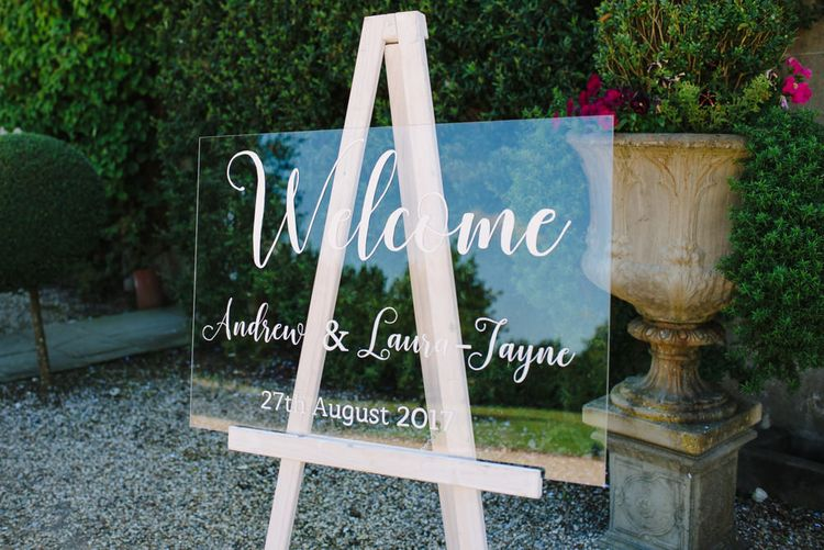 White Calligraphy Perspex Wedding Welcome Sign | Classic Pink & White Wedding at Northbrook Park, Surrey | Tell Your Story Photography | Yours Truly Wedding Films