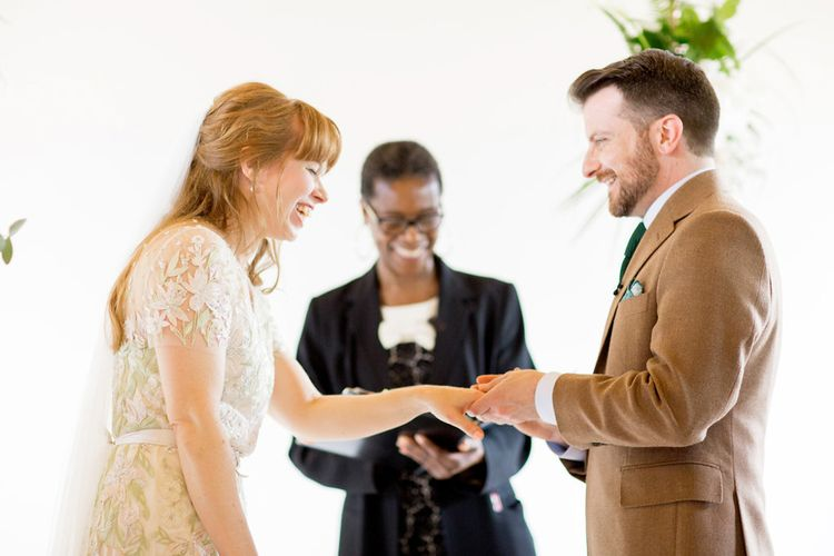 Bride in Jenny Packham Cassiopeia Wedding Dress with Groom in Brown Trousers and Blazer Exchanging Rings