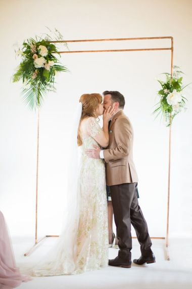 Bride in Jenny Packham Cassiopeia Wedding Dress with Groom in Brown Trousers and Blazer Kissing