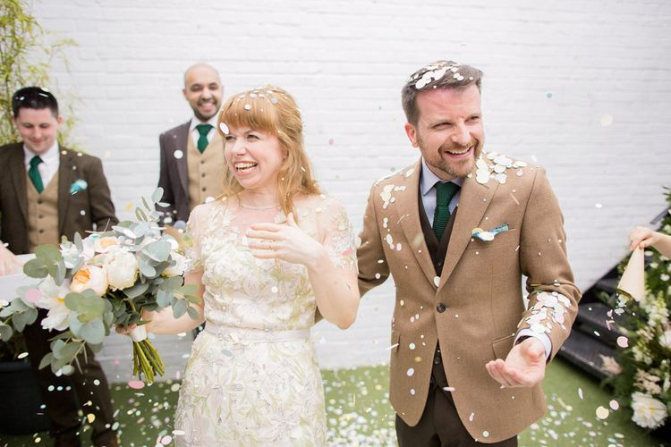 Confetti Moment with Bride in Jenny Packham Cassiopeia Wedding Dress with Groom in Brown Suit