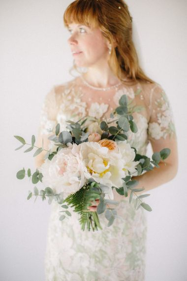 Bride in Light Pink and Green Floral Jenny Packham Wedding Dress Holding a White, Peach and Green Bouquet