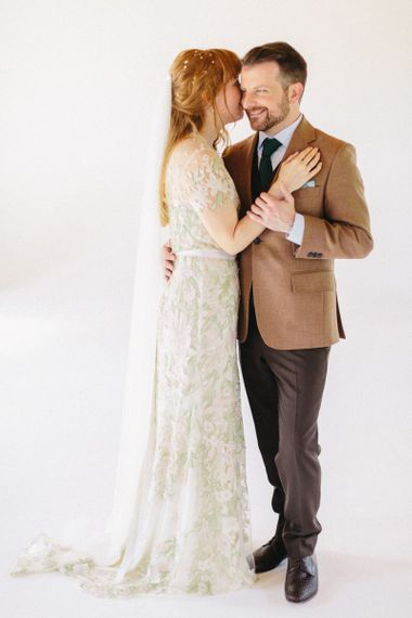 Bride in Jenny Packham Cassiopeia Wedding Dress with Groom in Brown Suit Embracing