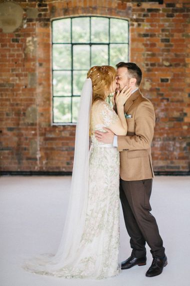 Bride in Jenny Packham Cassiopeia Wedding Dress with Groom in Brown Suit Kissing