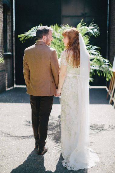 Bride in Jenny Packham Cassiopeia Wedding Dress with Groom in Brown Suit Holding Hands