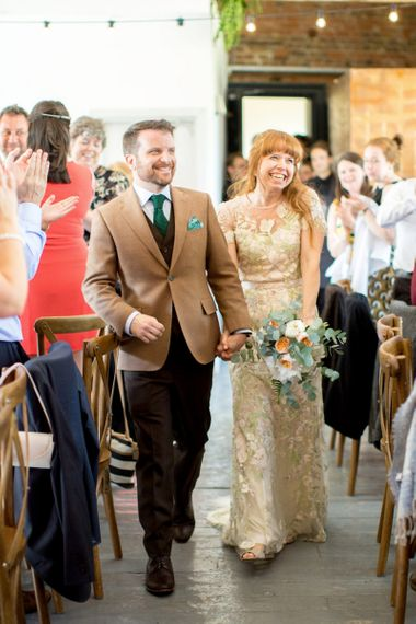Happy Bride in Jenny Packham Cassiopeia Wedding Dress with Groom in Brown Suit Entering the Wedding Breakfast