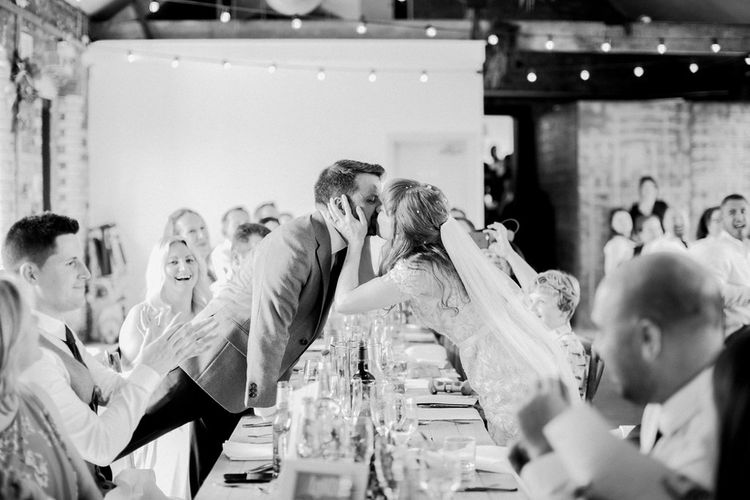 Bride and Groom Kissing During the Wedding Breakfast