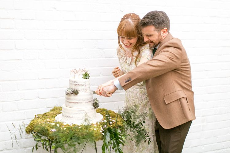 Bride and Groom Cutting the Semi Naked Wedding Cake on a Bed of Moss and Decorated with Succulents
