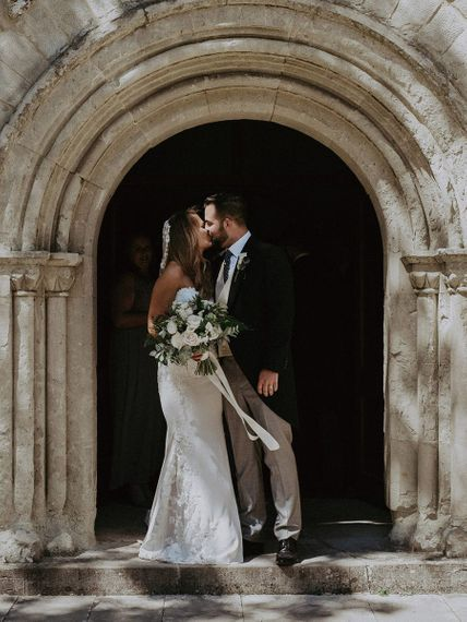 Bride and groom embrace outside of the traditional church ceremony in the Isle of Wight wearing lace edge veil