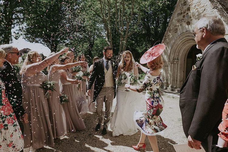 Bride and Groom confetti shot with bridesmaids wearing dusky pink dresses and white bouquets and bride wearing lace edge veil