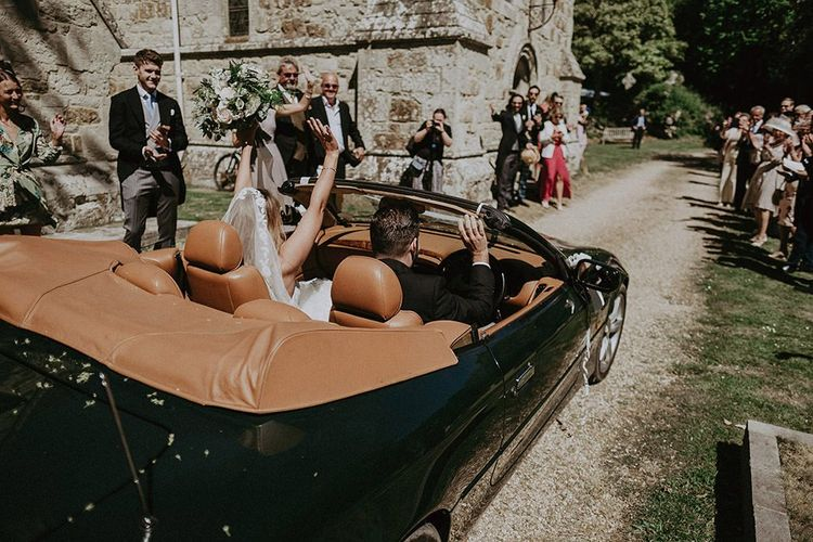 Bride and groom drive away in Aston Martin at summer English country wedding in the Isle of Wight wearing lace edge veil
