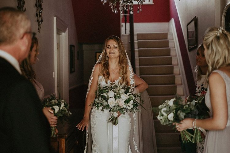 Bride wearing a lace edge veil and strapless wedding dress with white bouquet