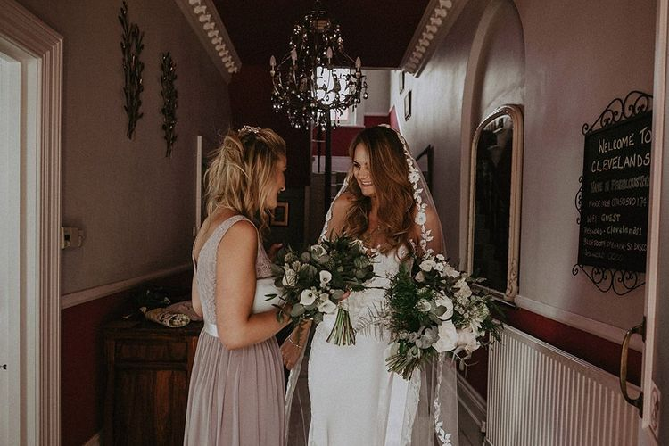 Bride wearing lace edge veil and bridesmaid in dusky pink dress