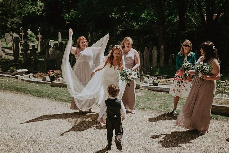 Bride wearing lace edge veil and strapless wedding dress with bridesmaids in dusky pink dresses