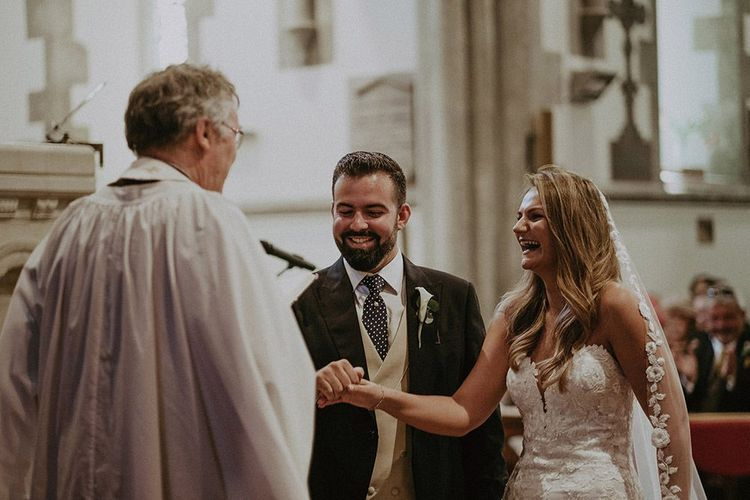 Bride wearing lace edge veil and groom in three piece suit tie the knot at a church wedding ceremony